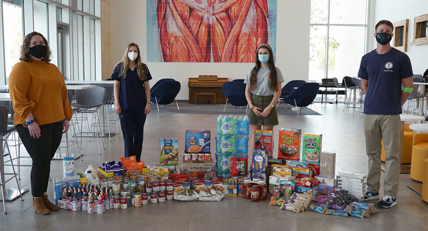 ICOM's Pediatrics Club students pose in front of collected food items.