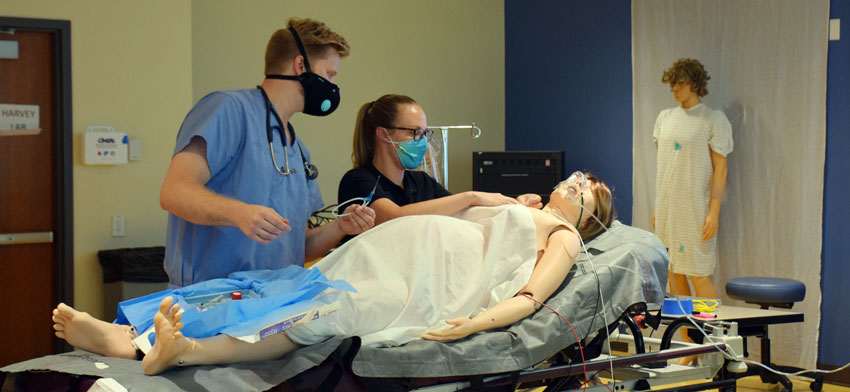 RVUCOM students practicing healthcare on a simulated patient.
