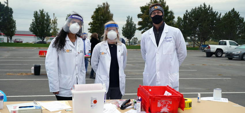 ICOM students in protective gear ready to administer flu shots