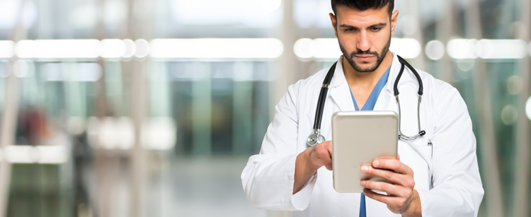 Doctor in white coat with stethoscope, looking at his tablet