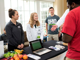 Students from the Heritage College, Athens, staff an information table in Ohio University's student center for NOM Week.