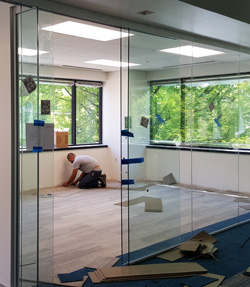 A workman lays carpet in one of AACOM's the new glass-fronted offices.