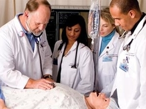 medical students overlooking a medical school instructor working on a dummy