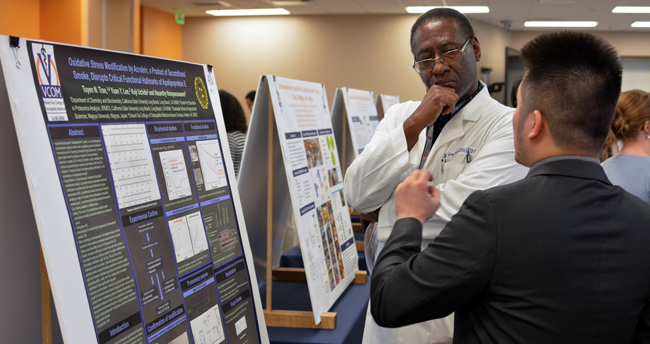 Student explaining poster to faculty